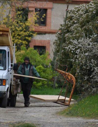 Patrick au monte charge qui permet de monter le bardage volige du futur caveau de vente en Ariège à Lézat sur Lèze